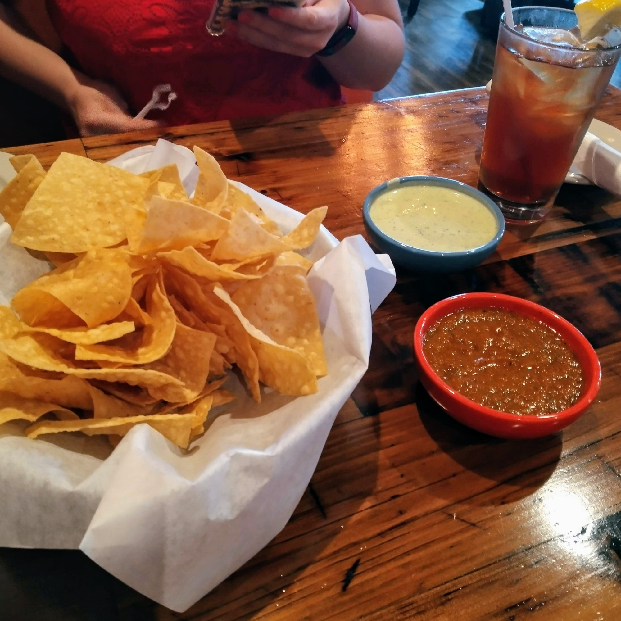 Chips-and-salsa-and-green-sauce-made-from-cilantro-sauce-from-taquilos-with-sweet-tea